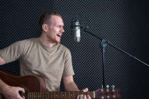 Young caucasian man sings while playing an acoustic guitar in front of black soundproofing walls. Musicians producing music in professional recording studio.