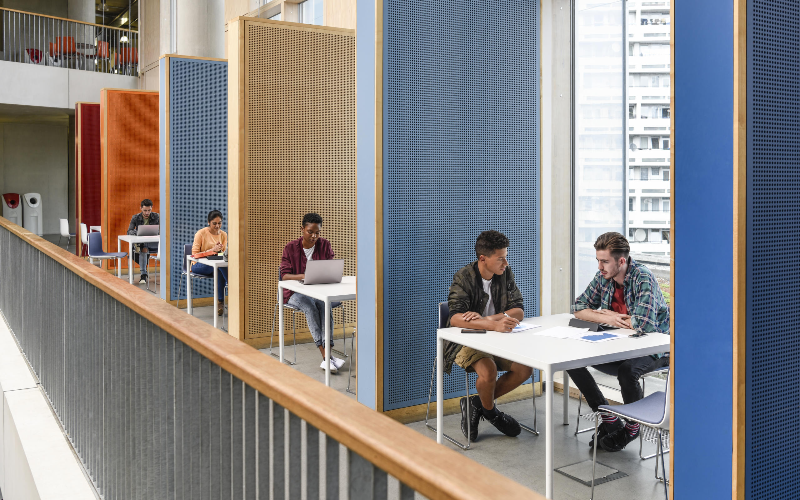 Row of colourful booths for student study, separated by partitions, providing privacy and space to work and meet